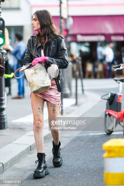 Guest wears a gold earring, a pale pink shiny satin short dress, a black shiny leather zipper jacket, a white crocodile pattern with beige leather...