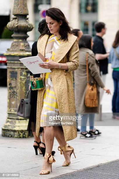 A guest wears a gold embroidered jacket a ruffled dress golden heels a green and golden bag outside the Schiaparelli show during Paris Fashion Week...