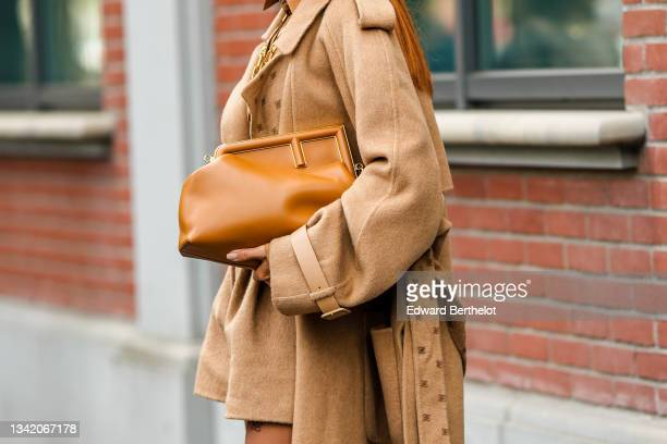 Guest wears a gold large chain FF necklace from Fendi, a brown with black stripes and FF monogram embroidered cropped shirt, beige ballon high waist...