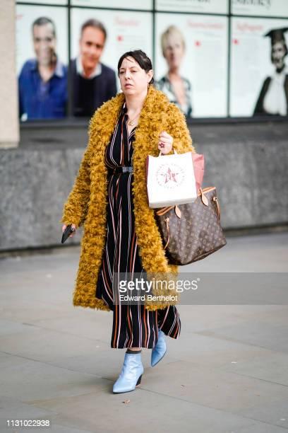 Guest wears a golden necklace, a honey color fluffy coat, a black flowing pantsuit with rust, white, pink color thin stripes, a Louis Vuitton...