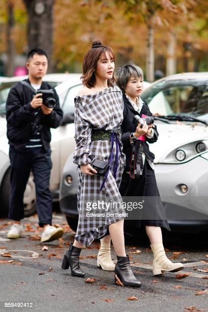 A guest wears a gray and white checked dress a black bag and black boots a guest wears a black trench coat and offwhite boots outside Manish Arora...