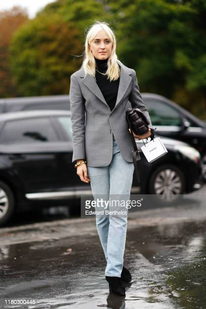 Guest wears a gray blazer jacket, a black turtleneck, pale blue denim pants, black shoes, outside Chanel, during Paris Fashion Week - Womenswear...