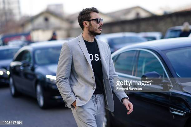 Guest wears a gray blazer jacket, a BOSS pullover, sunglasses, outside BOSS, during Milan Fashion Week Fall/Winter 2020-2021 on February 23, 2020 in...