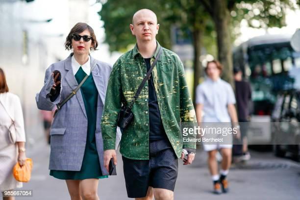 A guest wears a gray blazer jacket a green dress a guest wears a green jacket black shorts outside 1017 ALYX 9SM during Paris Fashion Week Menswear...