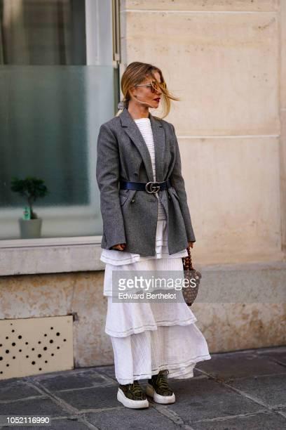 A guest wears a gray blazer jacket a ruffled white dress a Gucci belt outside Altuzarra during Paris Fashion Week Womenswear Spring/Summer 2019 on...