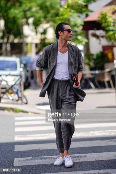 A guest wears a gray blazer jacket a white top gray cropped pants white sneakers outside Wooyoungmi during Paris Fashion Week Menswear SpringSummer...