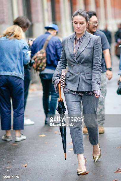 A guest wears a gray blazer jacket gray cropped suit pants siler shoes holds an umbrella outside Valentino during Paris Fashion Week Womenswear...