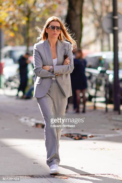 A guest wears a gray blazer jacket gray suit pants sneakers sunglasses outside Moncler during Paris Fashion Week Womenswear Spring/Summer 2018 on...