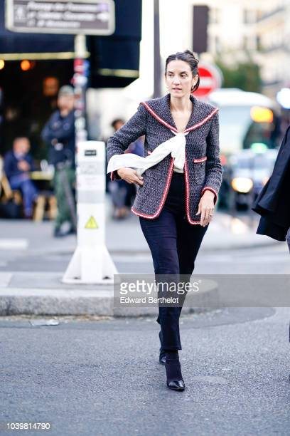 A guest wears a gray blazer jacket with pink borders outside Gucci during Paris Fashion Week Womenswear Spring/Summer 2019 on September 24 2018 in...