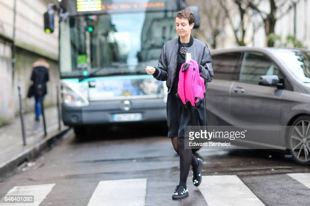 A guest wears a gray bomber jacket a pink backpack a black skirt black tights and black shoes outside the JOUR/NE show during Paris Fashion Week...