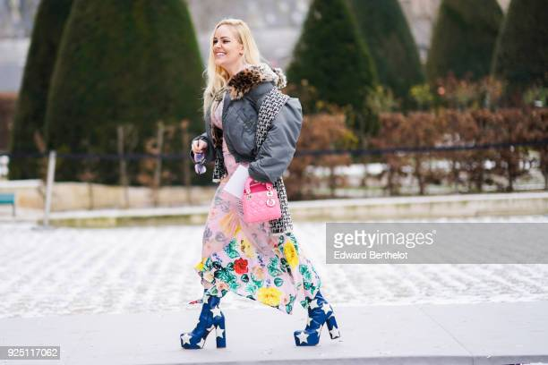 A guest wears a gray bomber jacket with leo print fur a color flower print dress a pink Lady Dior bag platform shoes with printed stars outside Dior...