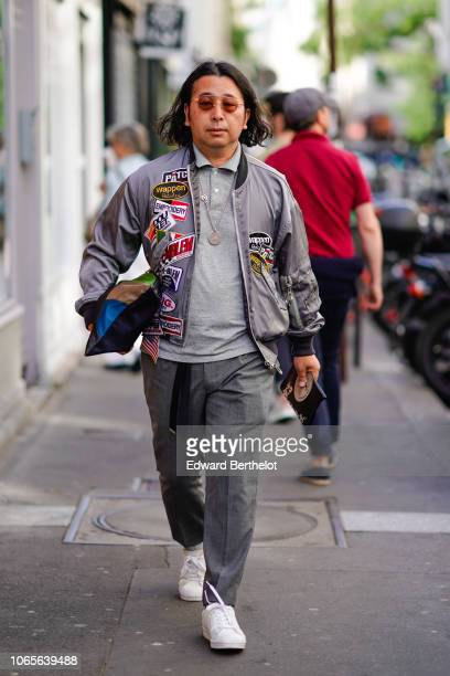 A guest wears a gray bomber jacket with patches a gray polo gray pants outside Yohji Yamamoto during Paris Fashion Week Menswear SpringSummer 2019 on...