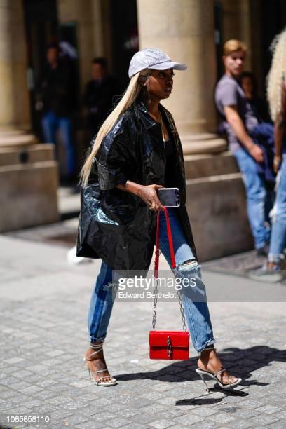 A guest wears a gray cap a black jacket a red bag blue ripped denim jeans silver heels shoes outside Louis Vuitton during Paris Fashion Week Menswear...
