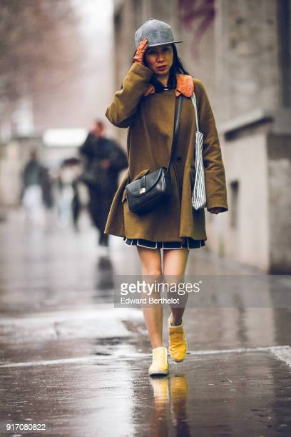 A guest wears a gray cap a dress yellow shoes a black leather bag under the rain outside Paul Smith during Paris Fashion Week Menswear Fall Winter...