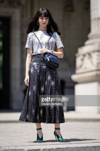 A guest wears a gray chanel tshirt a black skirt with white dots green heels shoes a Chanel blue bag outside the Chanel show during Paris Fashion...