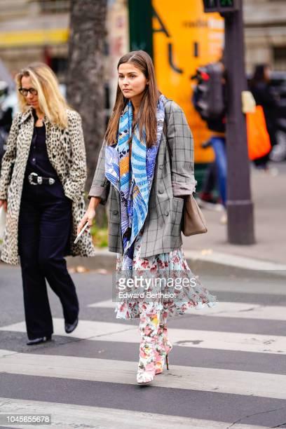 A guest wears a gray checked blazer jacket a blue scarf a floral print dress outside Miu Miu during Paris Fashion Week Womenswear Spring/Summer 2019...