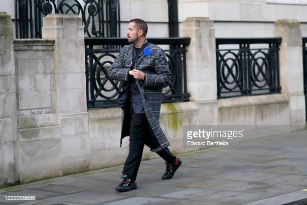 Guest wears a gray checked coat, black pants, sneakers, during London Fashion Week Fall Winter 2020 on February 16, 2020 in London, England.