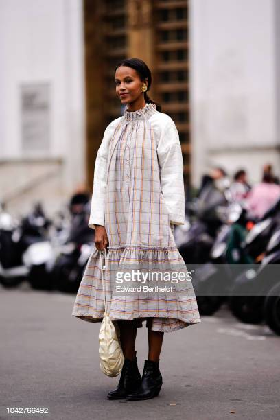 A guest wears a gray checked pleated dress a white circular bag outside Issey Miyake during Paris Fashion Week Womenswear Spring/Summer 2019 on...
