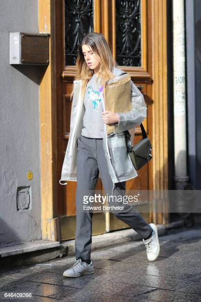 A guest wears a gray coat a gray pull over white shoes outside the AALTO show during Paris Fashion Week Womenswear Fall/Winter 2017/2018 on February...