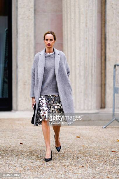 A guest wears a gray coat a gray pullover a silver shiny glitter skirt blue shoes outside Miu Miu during Paris Fashion Week Womenswear Spring/Summer...