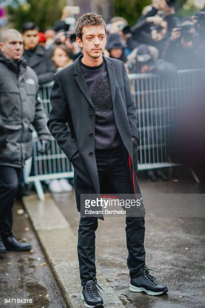 A guest wears a gray coat a pull over black pants sneakers shoes outside Dior during Paris Fashion Week Menswear Fall Winter 20182019 on January 20...