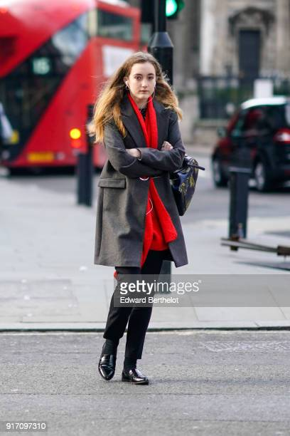 A guest wears a gray coat a red scarf during London Fashion Week Men's January 2018 at on January 6 2018 in London England