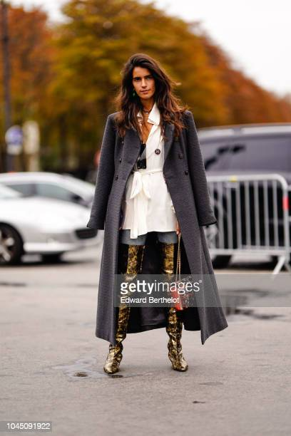 A guest wears a gray coat a white dress golden thigh high boots a red bag outside Chanel during Paris Fashion Week Womenswear Spring/Summer 2019 on...