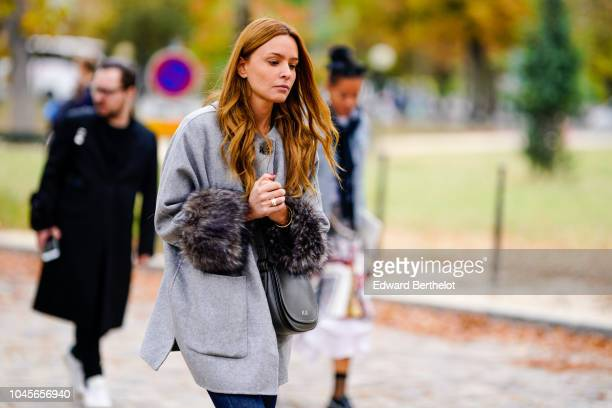 A guest wears a gray coat with faux fur on the sleeves outside Beautiful People during Paris Fashion Week Womenswear Spring/Summer 2019 on October 2...