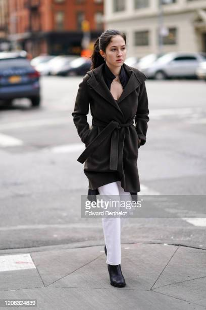 A guest wears a gray double breasted jacket white pants black leather shoes earrings a necklace during New York Fashion Week Fall Winter 2020 on...