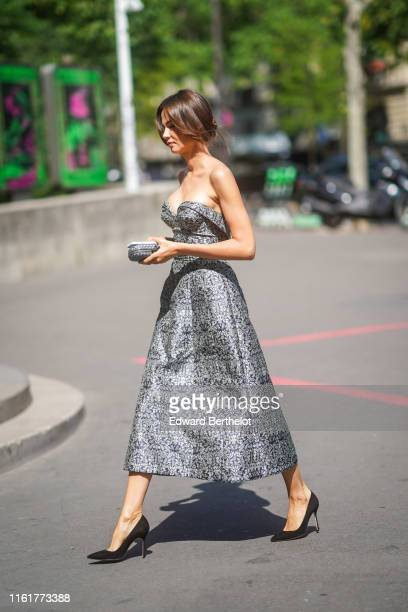 A guest wears a gray dress a clutch black pumps shoes during Paris Fashion Week Haute Couture Fall/Winter 2019/2020 on July 01 2019 in Paris France