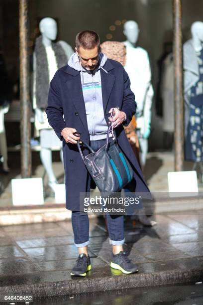 A guest wears a gray hoodie a blue long coat a bag and sneakers shoes outside the AALTO show during Paris Fashion Week Womenswear Fall/Winter...