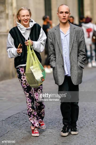 A guest wears a gray hoodie a yellow fishnet bag flower print pants red shoes a guest wears a blazer jacket a blue shirt black pants outside Koche...
