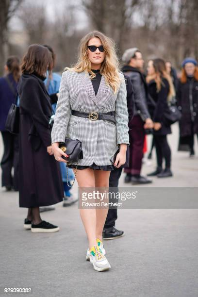 A guest wears a gray jacket a Gucci belt sneakers shoes a black bag outside Chanel during Paris Fashion Week Womenswear Fall/Winter 2018/2019 on...