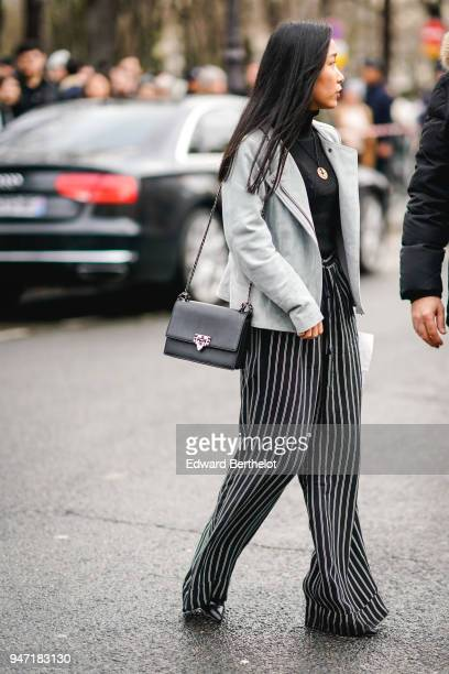 A guest wears a gray jacket black and white striped flare pants a black bag outside Dior during Paris Fashion Week Menswear Fall Winter 20182019 on...
