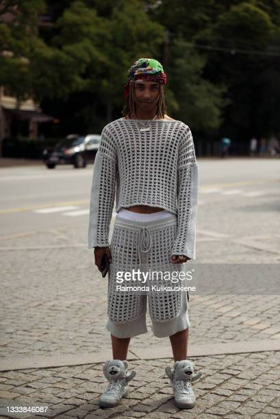 Guest wears a gray knit top and shorts and shiny silver sneakers with teddy bears outside MKDT during Copenhagen fashion week SS22 on August 12, 2021...