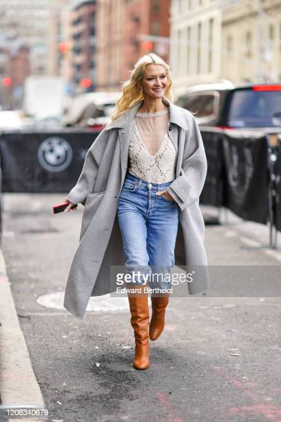 A guest wears a gray long coat a white lace mesh floral embroidery top blue denim jeans brown/orange leather boots during New York Fashion Week Fall...