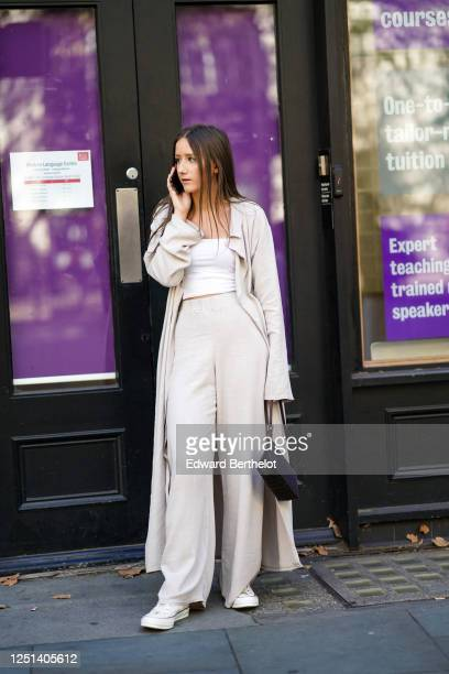 Guest wears a gray long coat, a white top, gray flared pants, white sneakers, a bag, during London Fashion Week September 2019 on September 13, 2019...