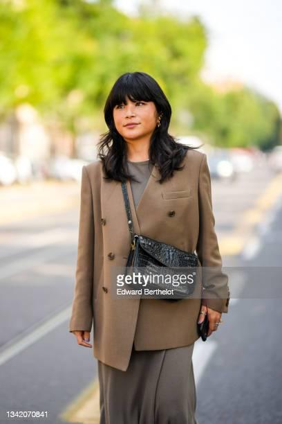 Guest wears a gray long flowing cotton dress, a brown oversized blazer jacket, a black shiny leather crocodile pattern crossbody bag, silver rings,...