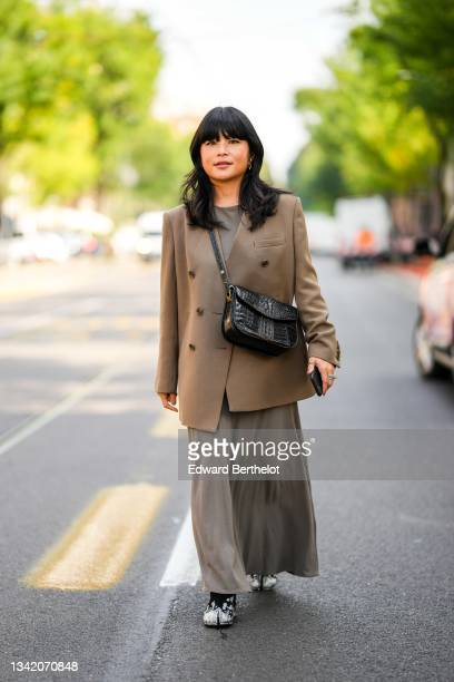 Guest wears a gray long flowing cotton dress, a brown oversized blazer jacket, a black shiny leather crocodile pattern crossbody bag, black and...