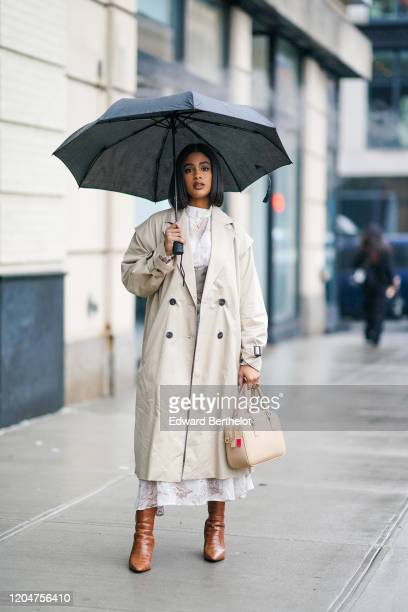 A guest wears a gray long trench coat a bag brown leather pointy crocodile pattern leather boots a white top a necklace an umbrella during New York...