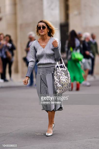A guest wears a gray low neck pullover a skirt a silver bag shoes outside Issey Miyake during Paris Fashion Week Womenswear Spring/Summer 2019 on...