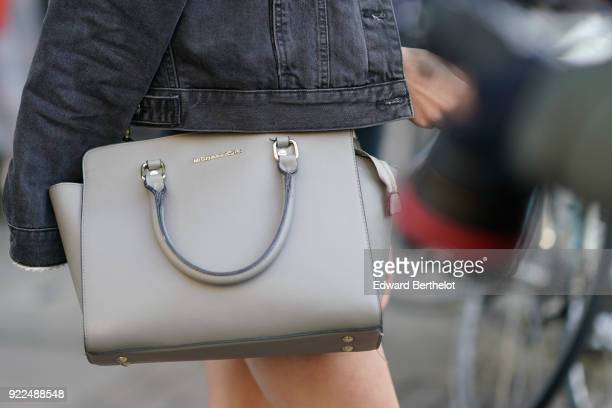 A guest wears a gray Michael Kors bag during London Fashion Week February 2018 on February 16 2018 in London England