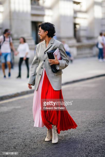Guest wears a gray oversized blazer jacket, a pink and red pleated skirt, beige boots with shoelace, a clutch, during London Fashion Week September...