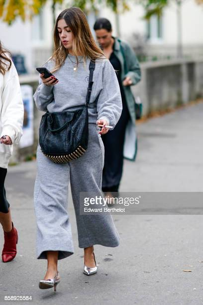 A guest wears a gray pull over a black bag gray flare oversize pants silver shoes outside Rahul Mishra during Paris Fashion Week Womenswear...