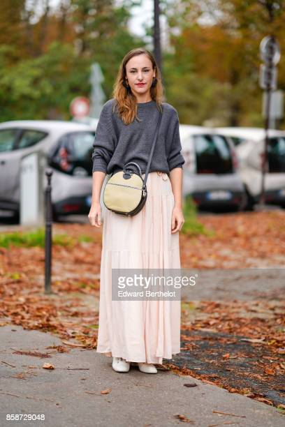 A guest wears a gray pull over a pink pleated skirt a circular bag outside Leonard during Paris Fashion Week Womenswear Spring/Summer 2018 on October...