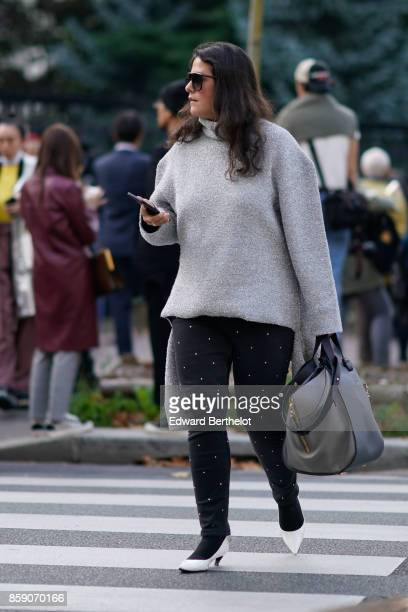 A guest wears a gray pull over oversize black pants white shoes gray bag outside CDG Comme des Garcons during Paris Fashion Week Womenswear...