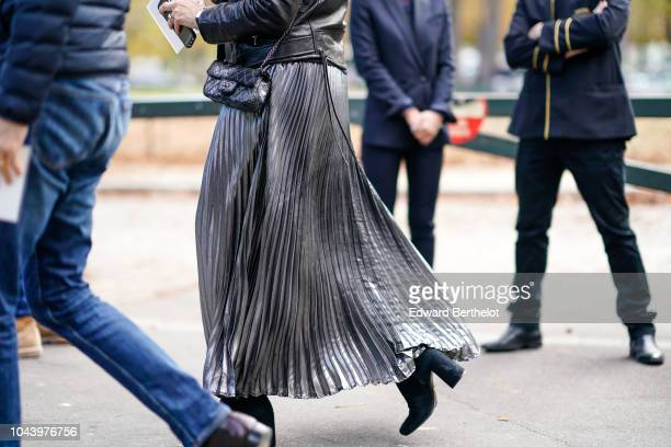 A guest wears a gray shiny pleated skirt outside Akris during Paris Fashion Week Womenswear Spring/Summer 2019 on September 30 2018 in Paris France
