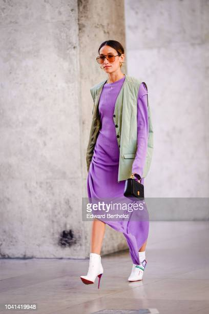 A guest wears a gray sleeveless jacket a purple dress white boots during Paris Fashion Week Womenswear Spring/Summer 2019 on September 26 2018 in...