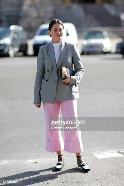 A guest wears a gray suit jacket and pink pants outside the Manish Arora show during Paris Fashion Week Womenswear Fall/Winter 2017/2018 on March 2...