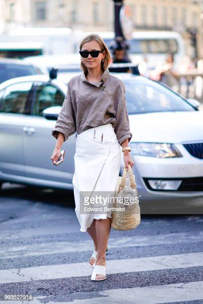 A guest wears a gray top a white skirt outside Schiaparelli during Paris Fashion Week Haute Couture Fall Winter 2018/2019 on July 2 2018 in Paris...